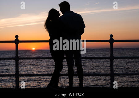 Aberystwyth Wales UK, Tuesday 02 July 2019  UK Weather: A couple embrace, silhouetted against the sky as they watch the glorious sunset in Aberystwyth on the Cardigan Bay coast, west Wales.   photo credit: Keith Morris//Alamy Live News - Stock Image
