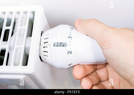 A Male Hand Turns The Radiator Of A White Heater In The Living Room, Saving Energy Concept - Stock Image