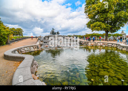 Tourists visit the Gefion Fountain featuring a large scale group of oxen driven by the Norse Goddess Gefjon in Langelinie Park, Copenhagen, Denmark. - Stock Image