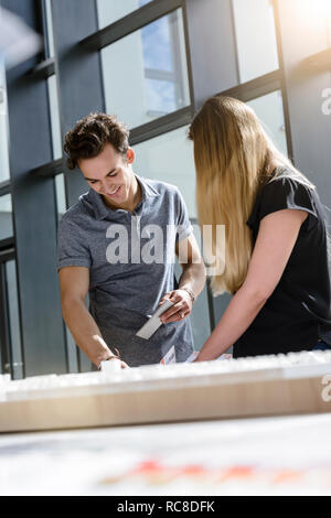 Colleagues brainstorming by glass wall - Stock Image