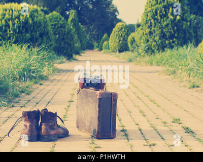 Ankle boots next to an old cardboard suitcase with a film camera on it. A yellow brick road, grass, and trees are visible in a blurry background. - Stock Image