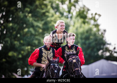 90th Kent County Show, Detling, 6th July 2019. Performers from The International Dzhigitovka. Two men on horseback carrying a woman. - Stock Image