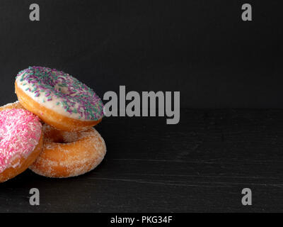 A pile of three ring donuts against a black background - Stock Image