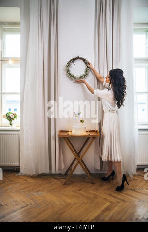 A woman hanging up a wreath on wall on indoor party, a cake on stand. Copy space. - Stock Image