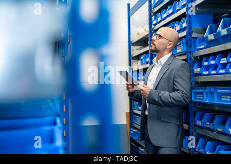 Businessman with tablet in factory storehouse - Stock Image