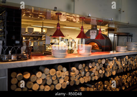 Wood logs for dome ceramic wood burning pizza oven in the kitchen of Amsterdam Brewhouse restaurant Toronto - Stock Image