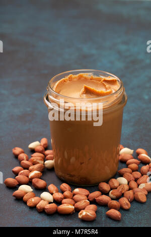 peanut butter in a glass jar, peanuts on a gray concrete background. - Stock Image