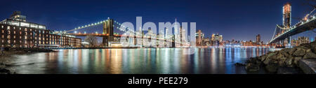 The skyscrapers of Lower Manhattan, the Brooklyn Bridge and the Manhattan Bridge in evening with the East River (panoramic). New York City - Stock Image