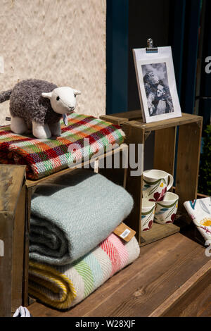 UK, Cumbria, Hawkshead, Flag Street, souvenir crafts, woven woolen blankets, toys, ceramic mugs, for sale outside National Trust shop - Stock Image