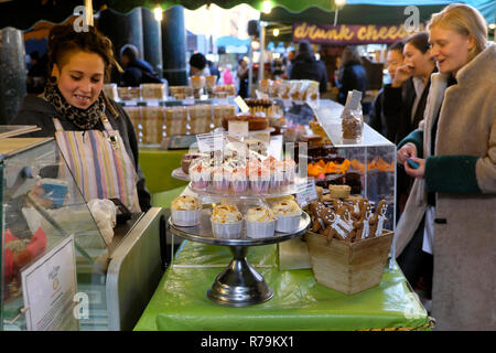 Young woman customer buying baked goods on a stall with gingerbread men and cupcakes in Borough Market in South London, England UK  KATHY DEWITT - Stock Image
