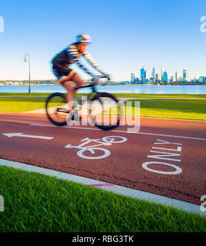 A male cyclist riding down a bike path with a city skyline in the distance - Stock Image