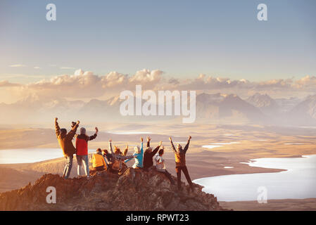Large group of happy friends is having fun on mountain top and looks at mountain's valley. Adventure or travel concept - Stock Image