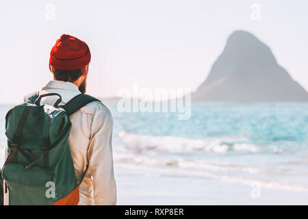 Summer vacations young man with backpack outdoor walking on ocean beach traveling lifestyle adventure enjoying landscape active trip exploring Norway - Stock Image