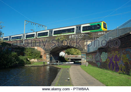 A West Midlands Railway train passes over the Birmingham & Fazeley Canal, in Aston in Birmingham, West Midlands, UK. - Stock Image