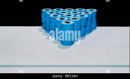 Pyramid of piles of blue poker chips on table with copy space - tournament poker chip leader - Stock Image