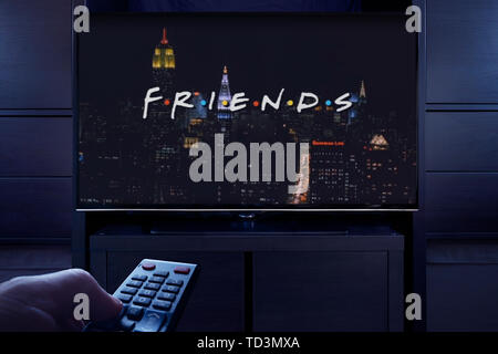 A man points a TV remote at the television which displays the Friends main title screen (Editorial use only). - Stock Image