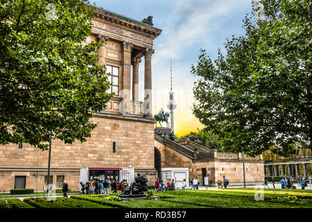 Tourists visit the National Gallery or Altes Nationalgalerie with the Fernsehturm TV Tower in view on Museum Island in Berlin Germany. - Stock Image