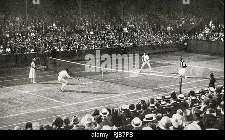 Mixed doubles match in progress on Centre Court at the old Wimbledon ground, SW London, before it moved to larger premises in 1922. - Stock Image