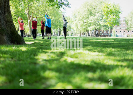 Active seniors exercising, practicing yoga in park - Stock Image
