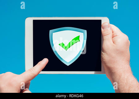 Man holding a tablet device pointing at an anti-spam, security firewall icon and touching the screen with a finger with blue sky in background. - Stock Image
