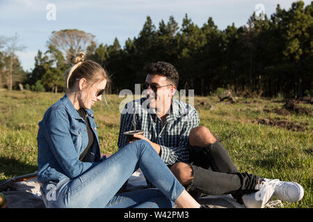 man and woman with glasses, with mate in hand, picnic day, under the sun - Stock Image
