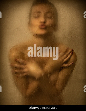 Naked young woman in the shower with arms crossed blowing a kiss at camera - Stock Image