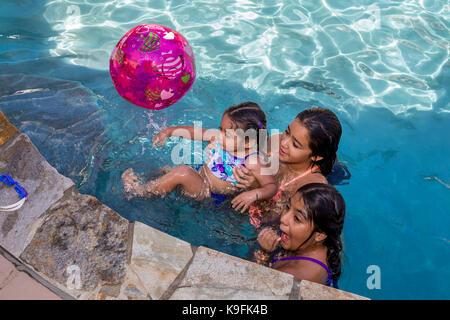 3, three, Hispanic girls, playing in swimming pool, swimming pool, fresh water swimming pool, Castro Valley, Alameda - Stock Image