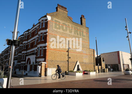 Man on bike cyclist cycling in Windrush Square and the Bovril building next to Black Cultural Centre in Brixton South London England UK  KATHY DEWITT - Stock Image
