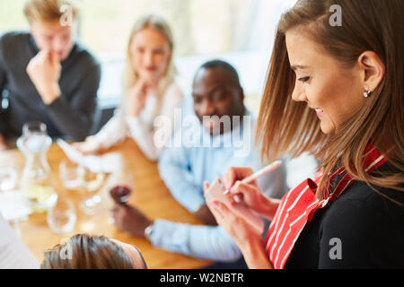 Young waitress in the restaurant notes the order of guests on a notepad - Stock Image