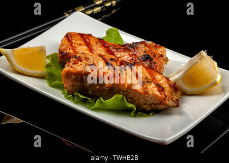 Fish, trout, chum salmon, humpback, a piece baked, grilled, with a slice of lemon and lettuce - Stock Image