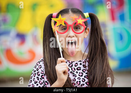 Fun young girl sticking out her tongue as she holds a party accessory of colorful glasses with stars to her eyes against a multicolored background - Stock Image