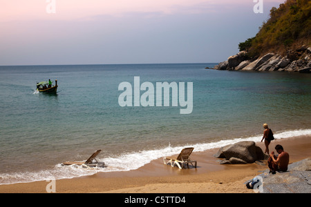 Long-tail boat approaching beach with couple on beach and two empty sunbeds at water's edge on Paradise Beach. - Stock Image