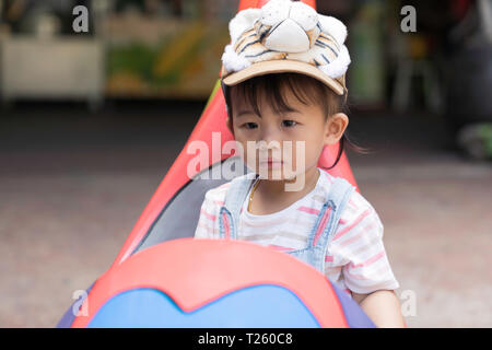 Asian kid girl is happiness in car toy, family travel concept. - Stock Image