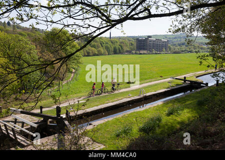 Family cycling past lock at Scarwood Bridge on the Huddersfield Narrow Canal at Linthwaite, West Yorkshire - Stock Image
