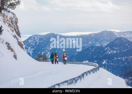 Friends hiking out after back country snowboarding and skiing. - Stock Image