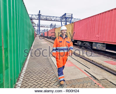 Dock worker walking by cargo train - Stock Image