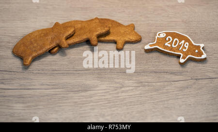 New Year piggy for good luck from Xmas gingerbread cookie. Cute golden pig shaped sweets decorated by icing. On wood background. For happiness in 2019. - Stock Image