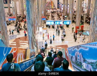 People arriving into the main arrival hall at Dubai international airport UAE - Stock Image