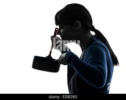 one  woman smelling cooking in silhouette studio isolated on white background - Stock Image