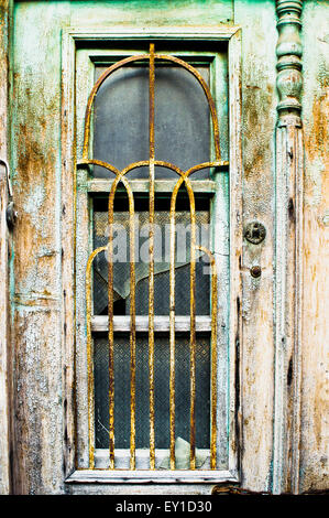 An old wooden window with broken glass and rusty metal bars - Stock Image
