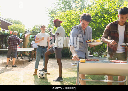 Male friends enjoying barbecue in sunny summer backyard - Stock Image