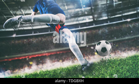 Football scene at night match with player kicking the ball with power - Stock Image