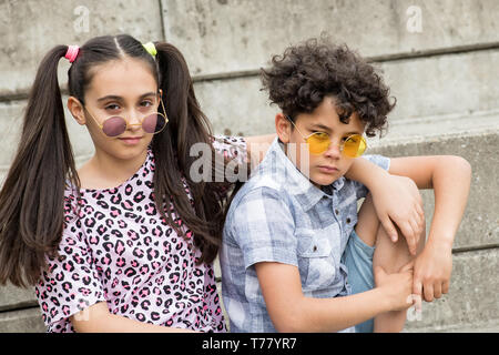 Trendy young brother and sister wearing modern colored circular sunglasses sitting arm in arm on outdoor steps looking at camera with serious expressi - Stock Image