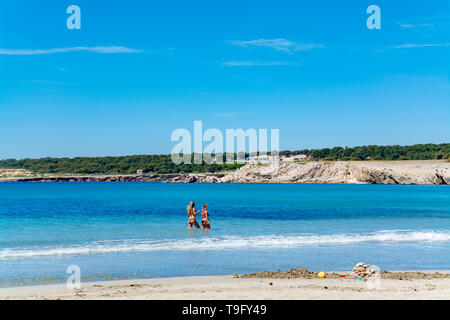 Crystal clear blue water of  Mediterranean sea on St.Croix Martigues white sandy and two undefinad women, Provence, France, vacation destination - Stock Image