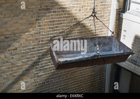 empty construction bucket on hoist on side of brick building - Stock Image