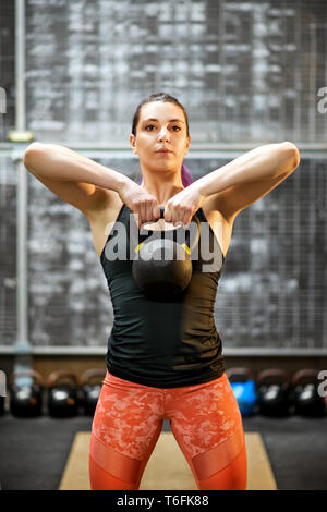 Young female athlete holding a kettlebell weight with both hands raised to her chest during a workout in a gym in a close up frontal view - Stock Image