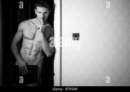 Nude muscular man covers his modesty with book while holding a finger to his lips - Stock Image