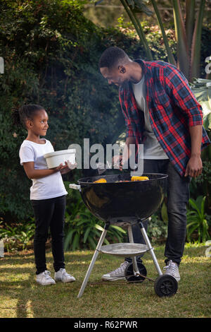 A girl helping her dad at a barbecue - Stock Image