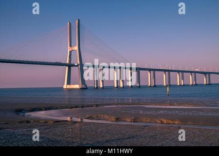 Vasco da Gama Bridge (Ponte Vasco da Gama) spans the Tagus River in Parque das Nacoes, Lisbon, Portugal - Stock Image