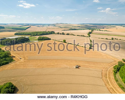 Harvest aerial landscape of combine harvester cutting summer wheat field farm crop tractor trailer and blue sky - Stock Image